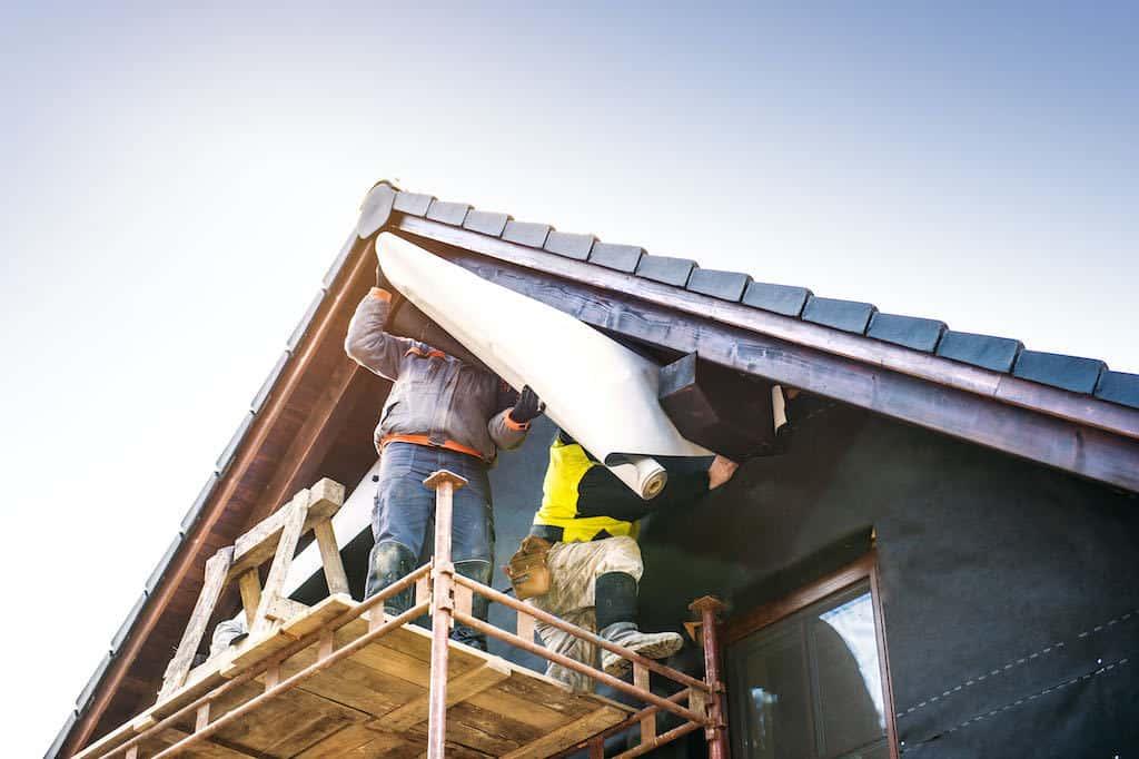 Håndværkere renovere facade på hus