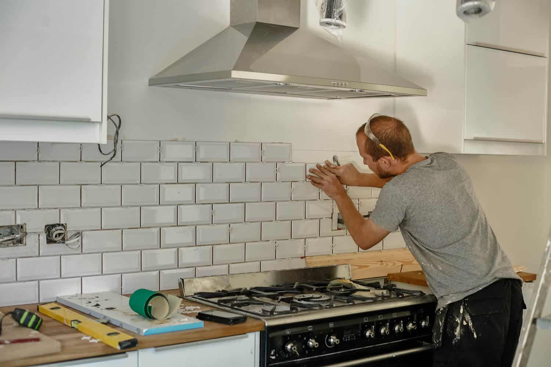 håndværker fuger fliser i køkken