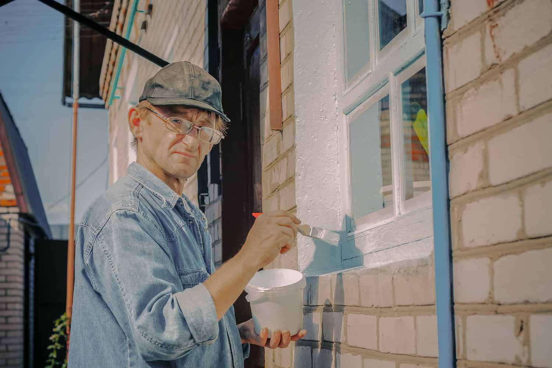 Mand maler vinduer